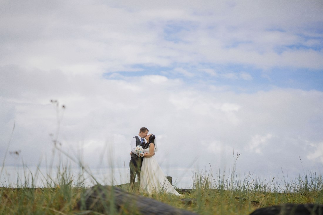 Iona Beach Wedding Couple embrace under cloudy sky in Vancouver