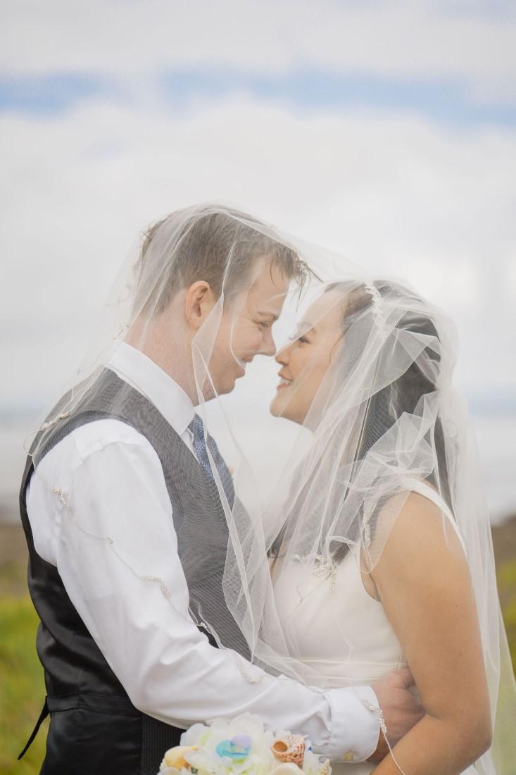 Bride and groom under veil by David's Bridal Vancouver