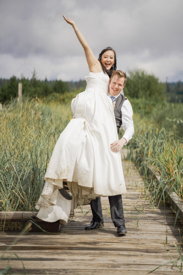 Newlyweds cheer on Vancouver Beach Boardwalk by Chuunice Photography