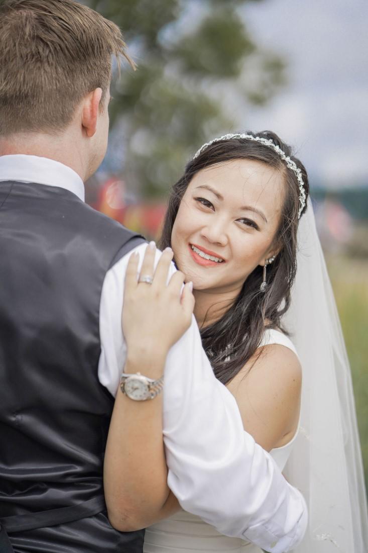 Bride smiles over her husbands shoulder at Vancouver Beach Wedding