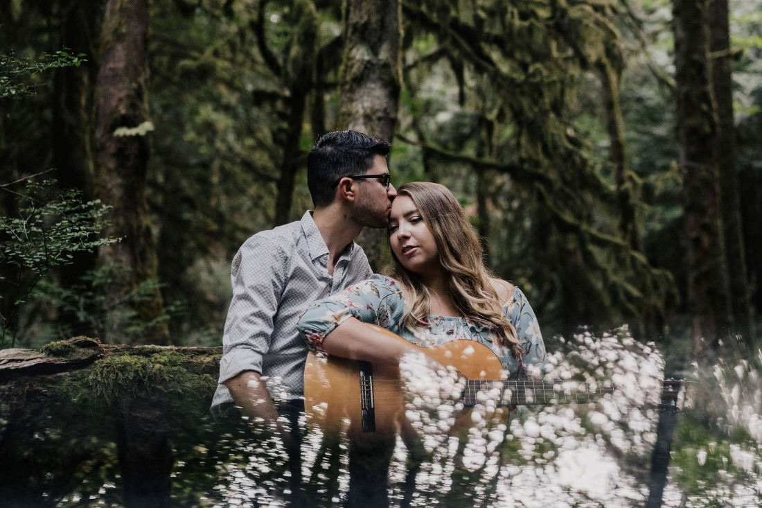 Couple embraces while playing guitar at Gowlland Tod Park on Vancouver Island