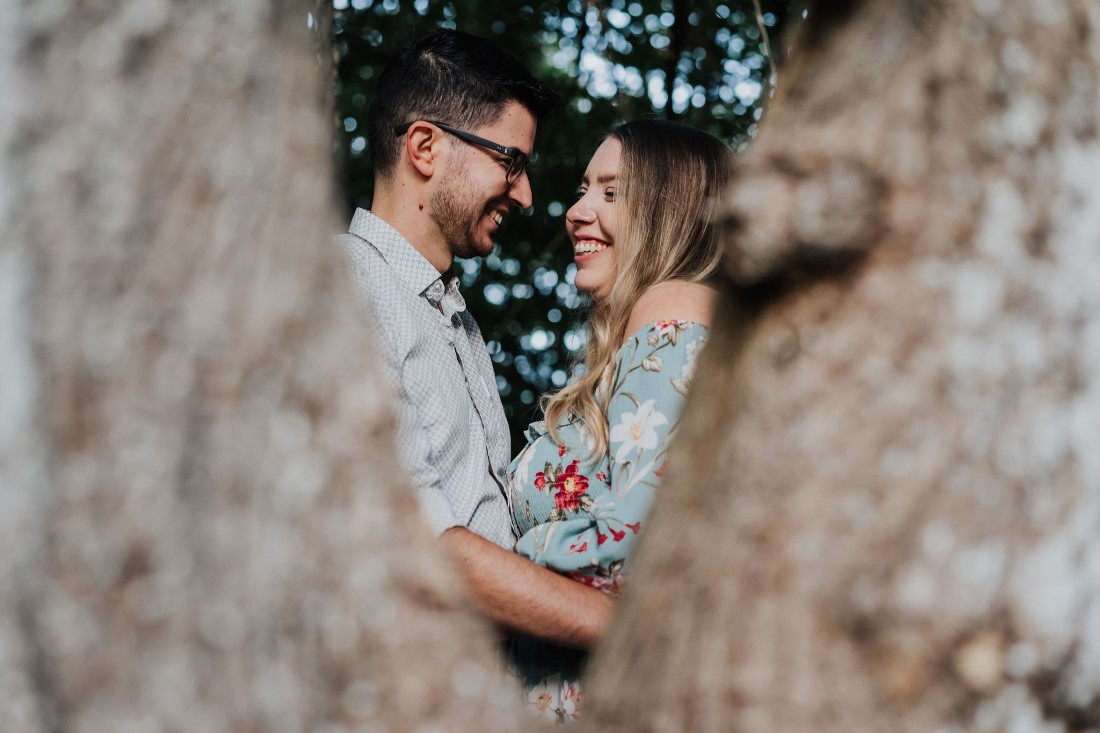 Engaged couple smiling at each other through tree shot on Vancouver Island