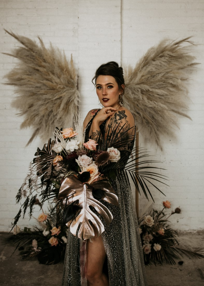 Bride holding bouquet with Pampas grass wings