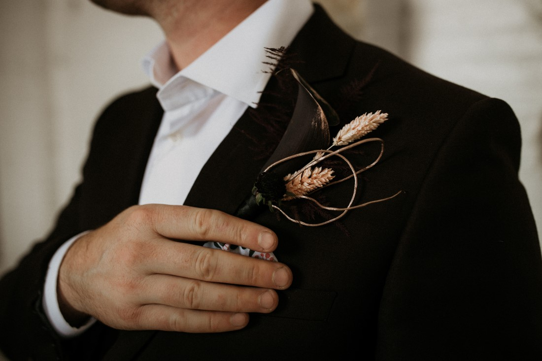 Groom in black suit with boutonniere of grass and peach roses by Bespoke Blossoms Vancouver Island