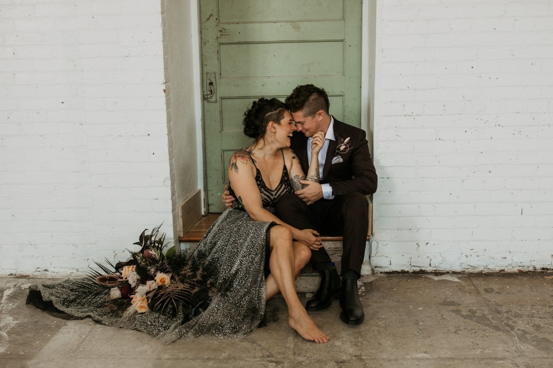 Newlyweds sit in vintage green doorway by Secret Waters Photography