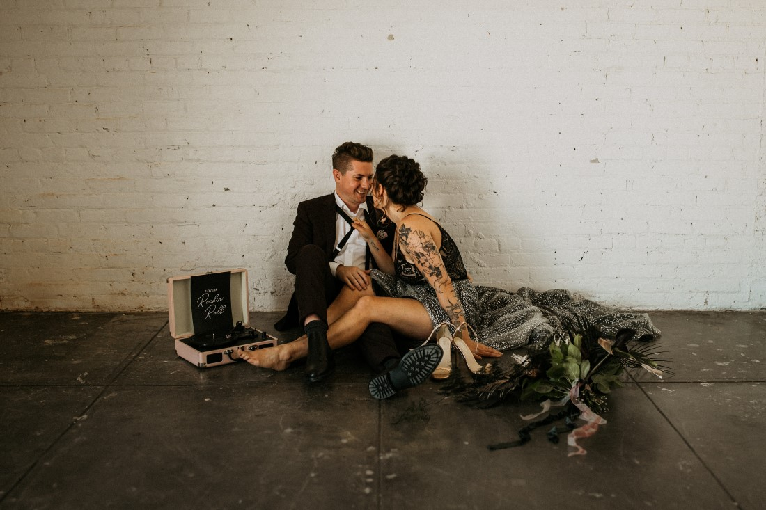 Bride kisses groom while they sit on the floor