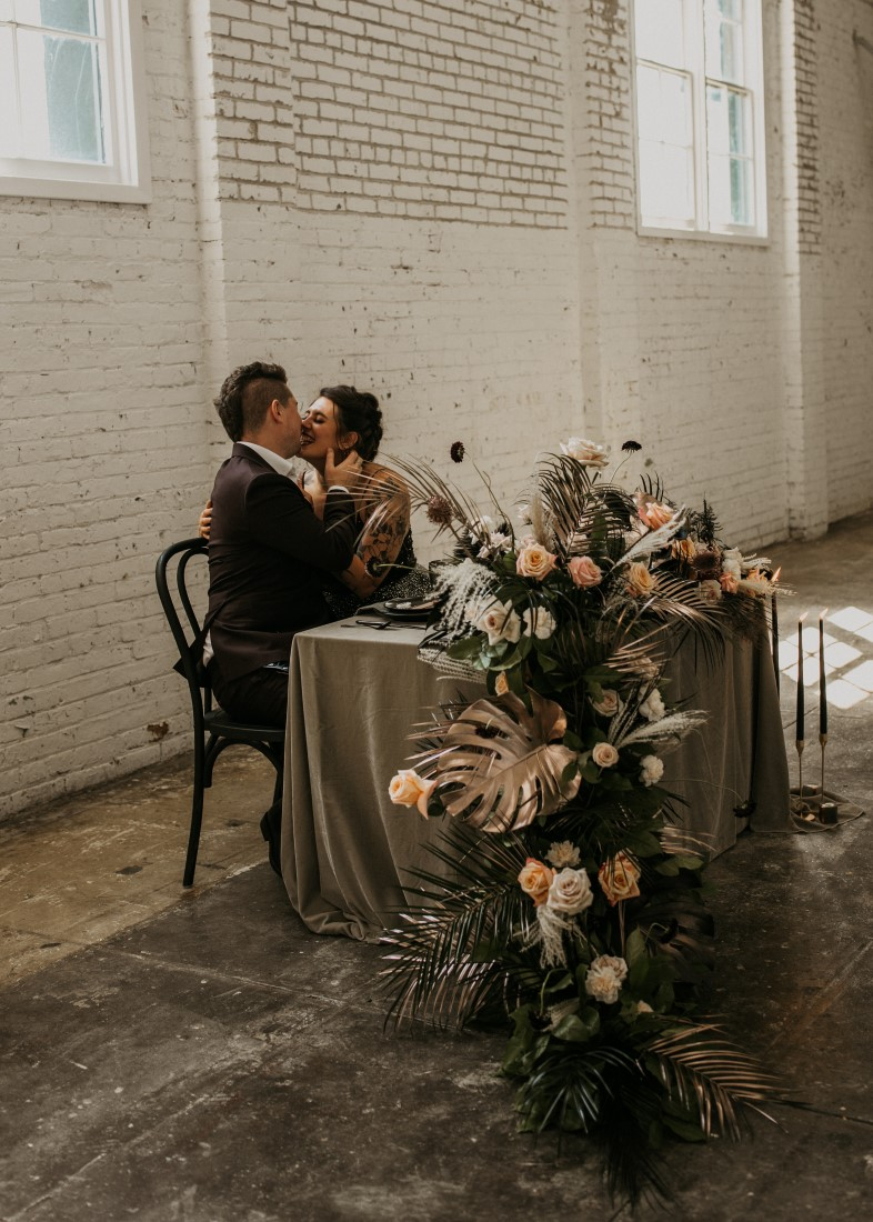 Bride and groom kiss at sweetheart table with floral cascading off the edge