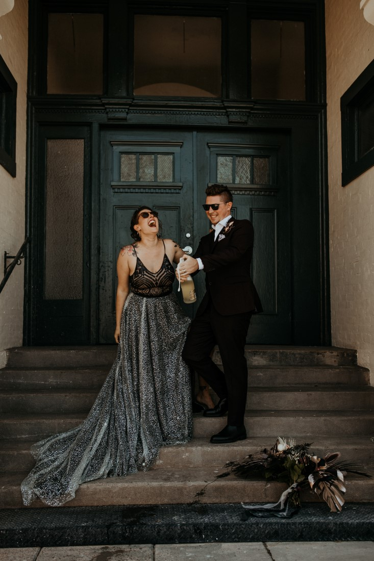 Newlyweds wearing grey and black on the steps of Powerhouse on Vancouver Island