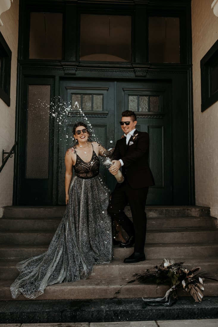 Newlyweds open bottle of champagne on the steps of Powerhouse Industrial Chic venue on Vancouver Island