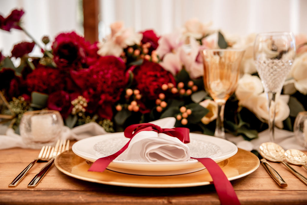 Napkin sits on gold charger with pink orchids behind at Pacific Gateway wedding