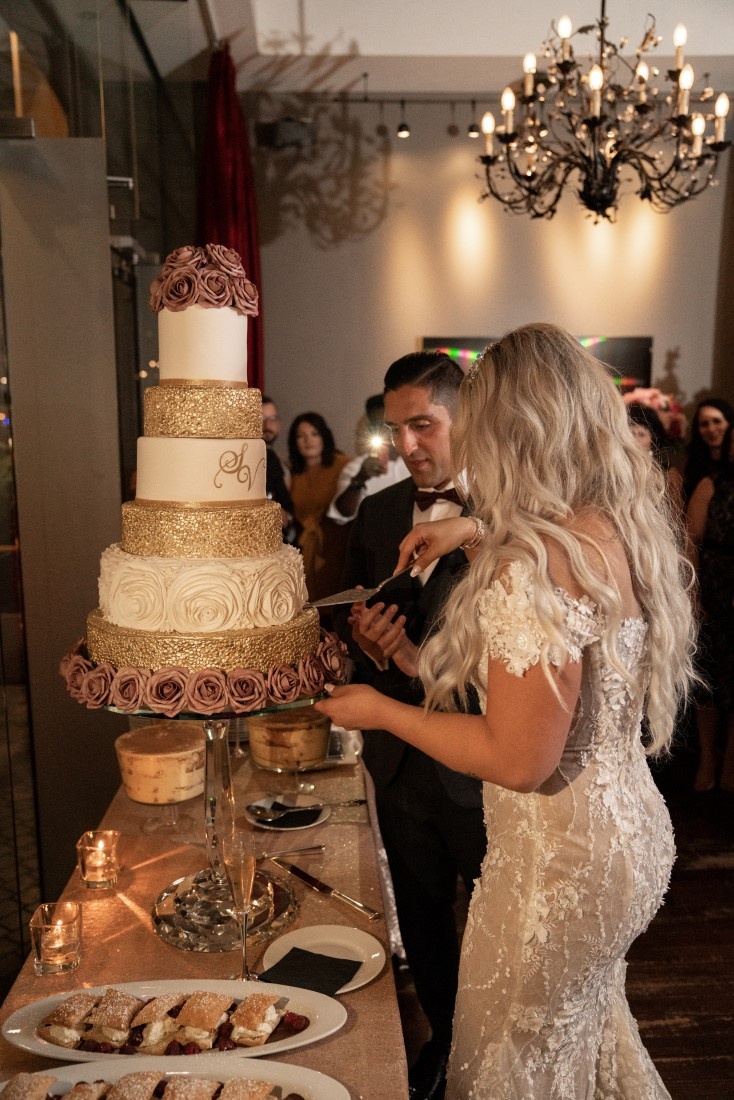 Persian Newlyweds cut five tiered gold and white wedding cake at Hatley Castle