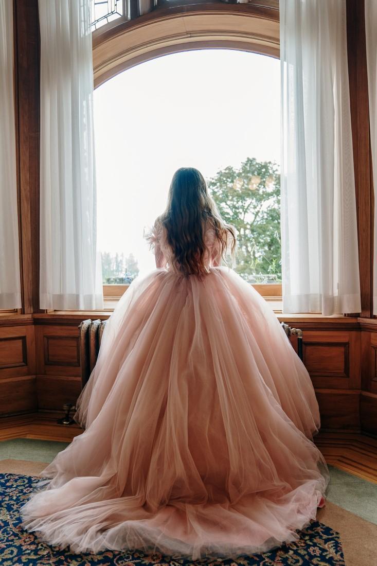 Bride looks out Hatley Castle window in her Pronovias wedding gown
