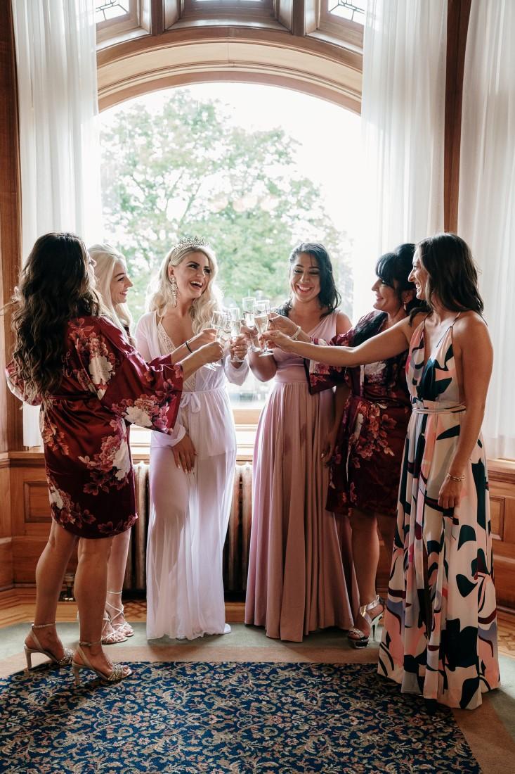 Bridesmaids help bride into her gown at Hatley Castle