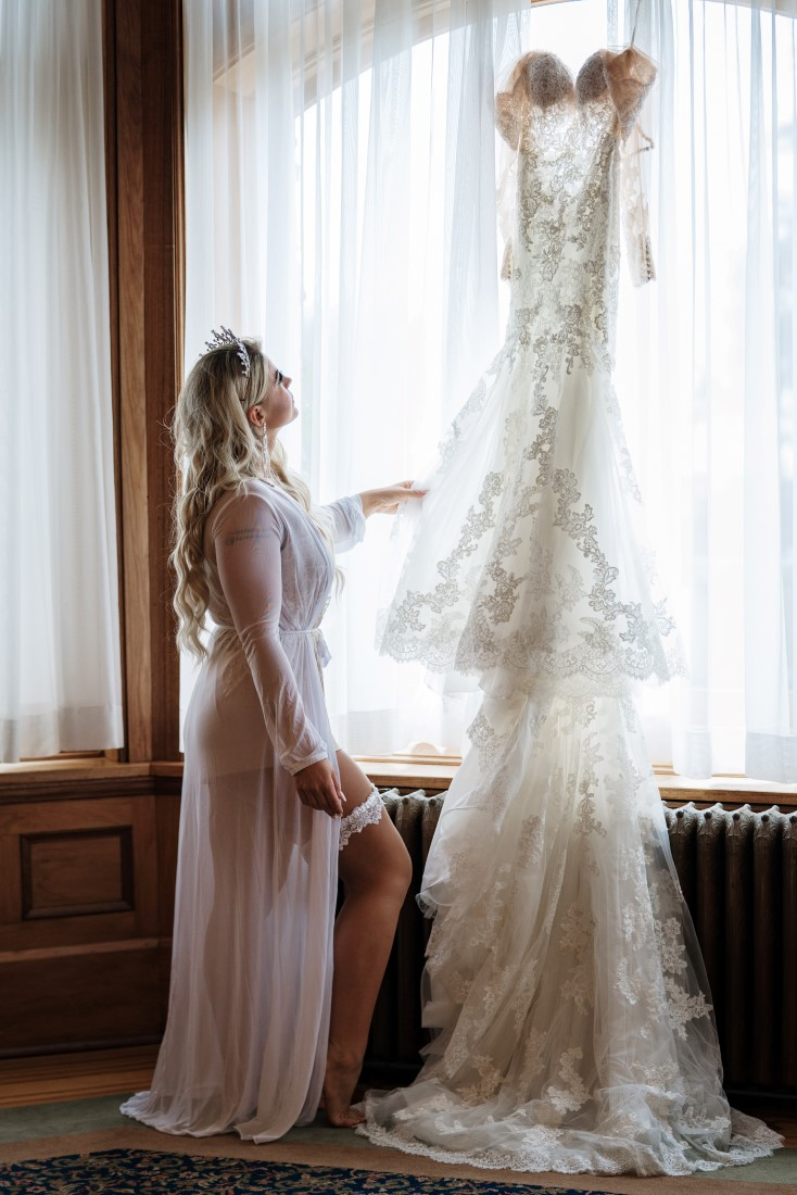 Bride touches the lace on her Pronovias wedding gown hanging in the window of Hatley Castle