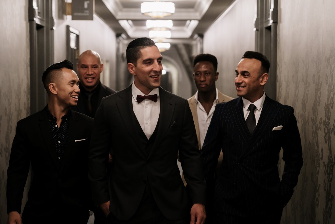 Groom and groomsmen in tuxes and bowties walk down Hatley Castle hall