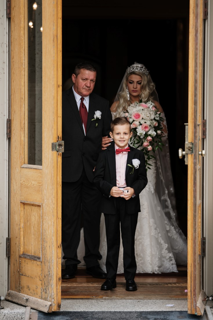 Castle Garden Wedding bride comes out of Hatley Castle doors with father and ringbearer