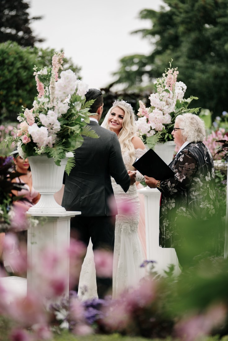 Bride and groom kiss after their vows at Hatley Castle Gardens