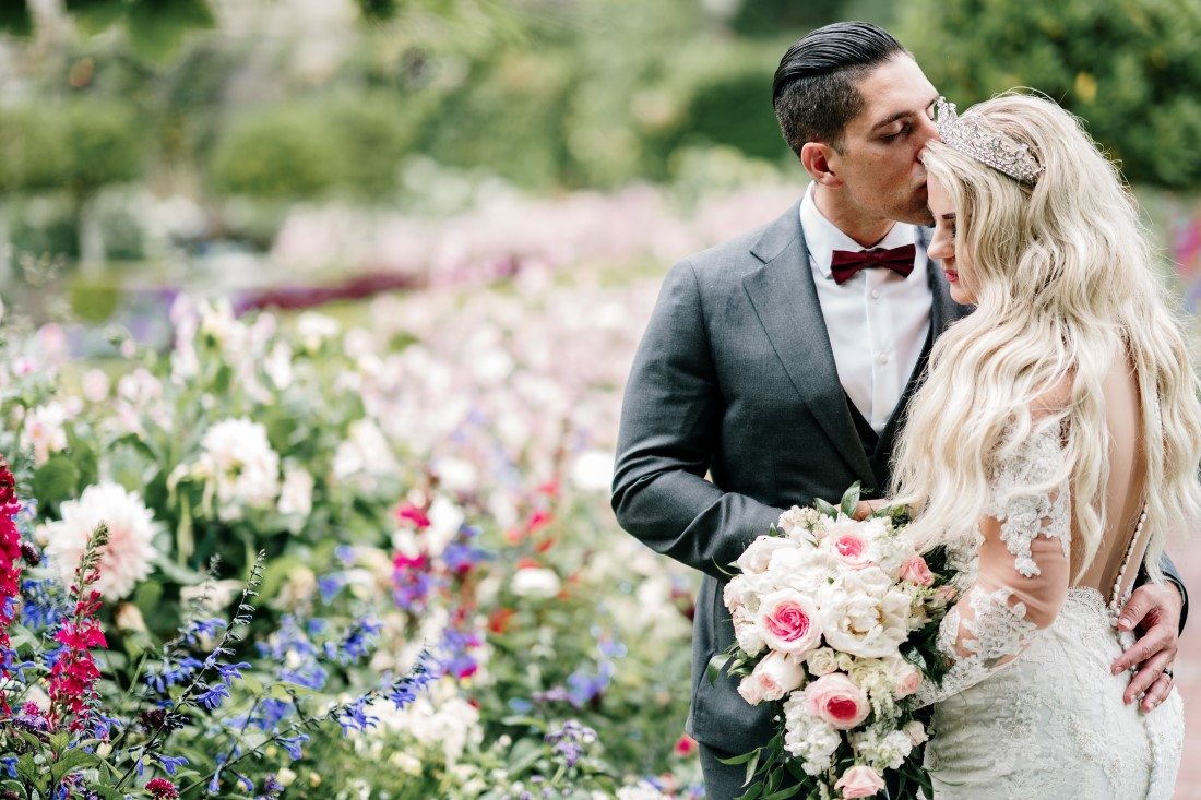 Newlyweds in Hatley Castle Gardens surrounded by flowers by Ross Kyker Photography
