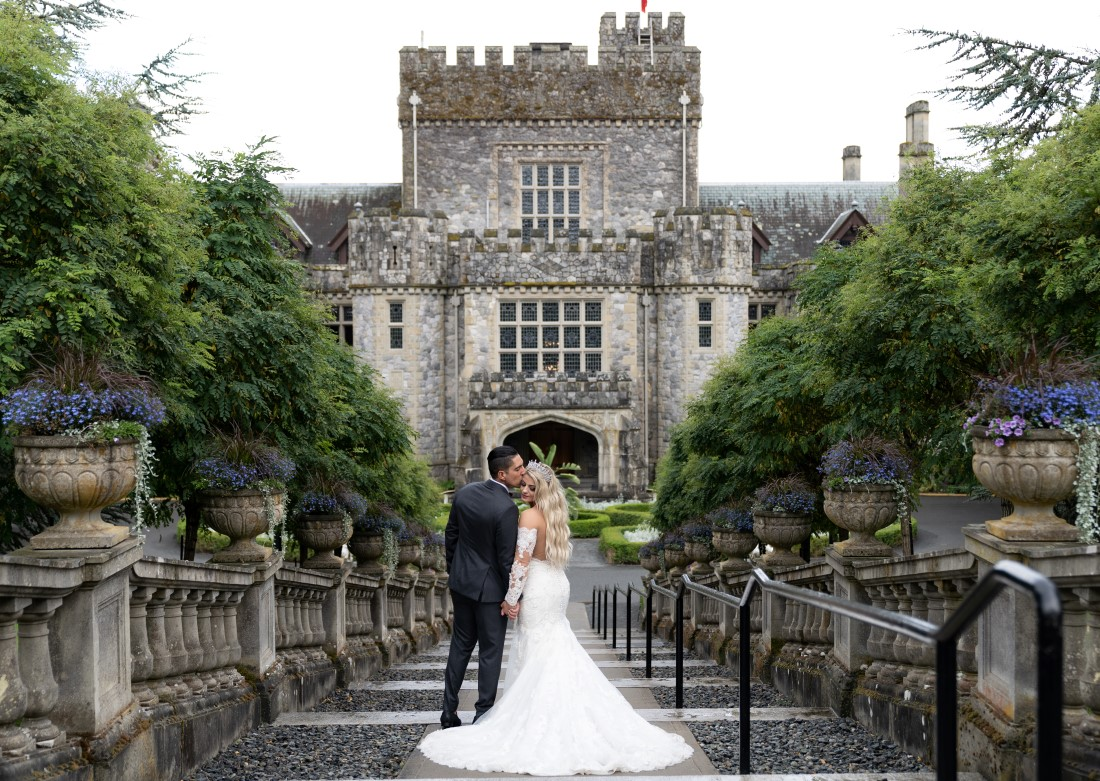 Newlyweds pose in front of Hatley Castle on Vancouver Island by Ross Kyker Photography