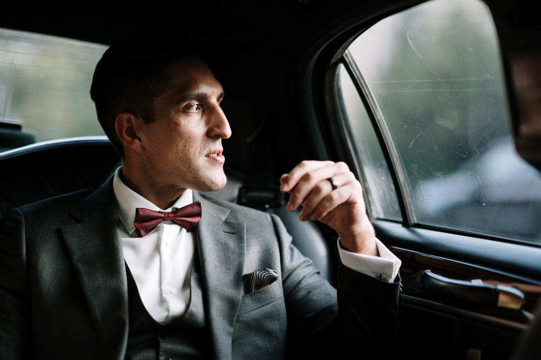 Groom wearing Indichino grey suit sits in limousine by Ross Kyker Photography