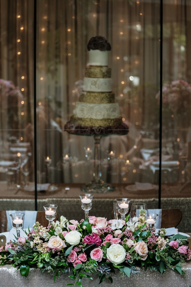 Zambris Wedding Reception Table filled with floral and five tiered wedding cake behind