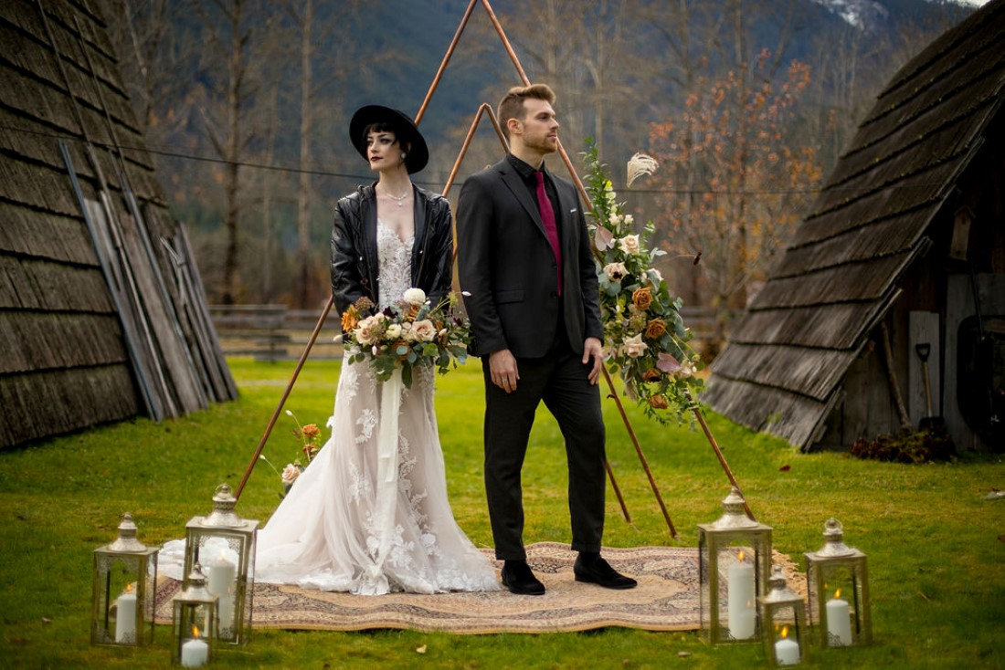 Bride and Groom in front of ceremony decor and backdrop of BC mountains