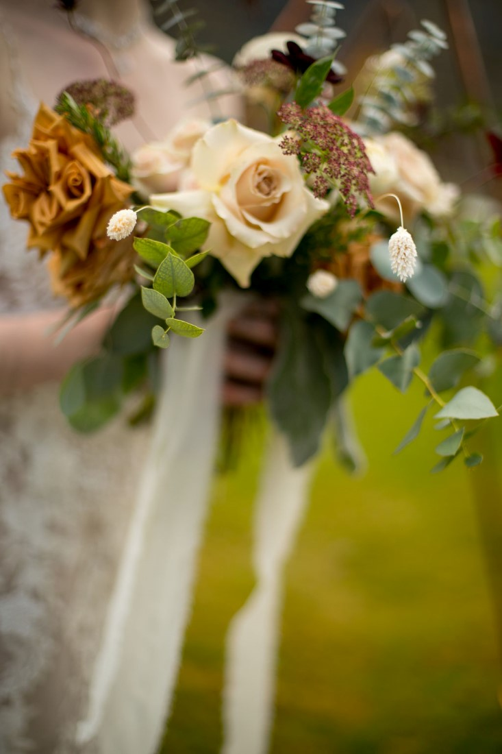Bridal bouquet of pale roses, long white ribbons and greenery