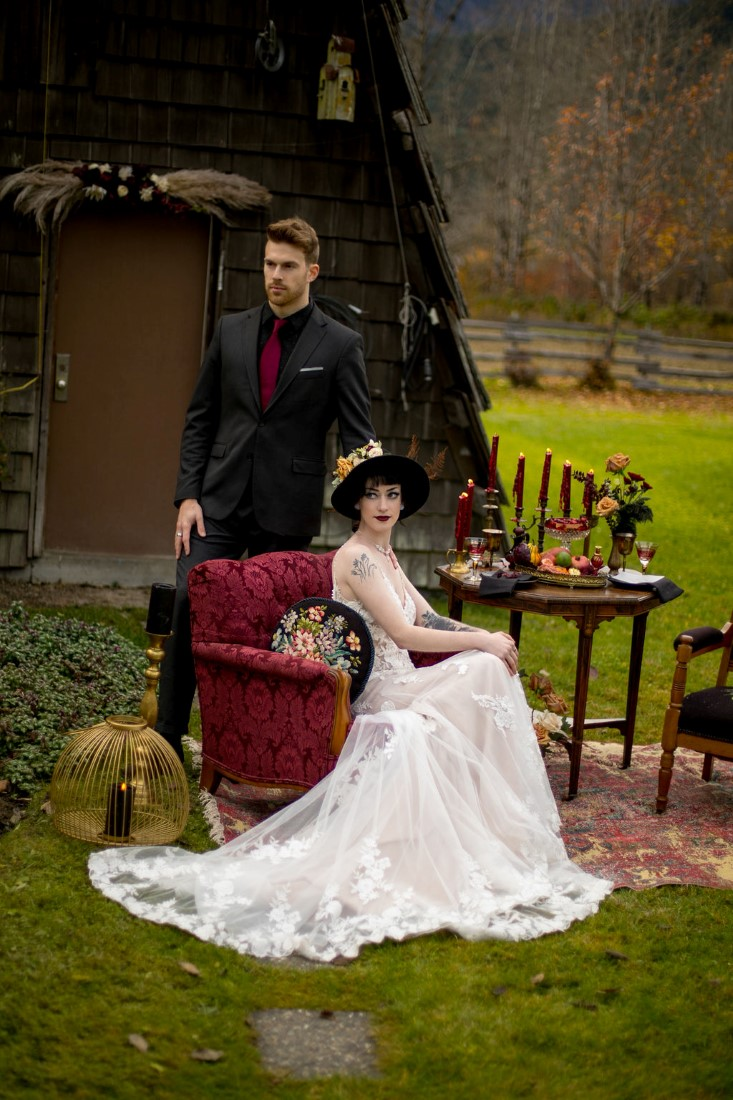 Newlyweds sit on red velvet hair in front of Vancouver mountains
