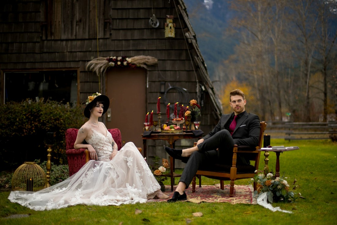 Breathtaking Wedding Beauty newlyweds sit in front of BC cabin and mountains