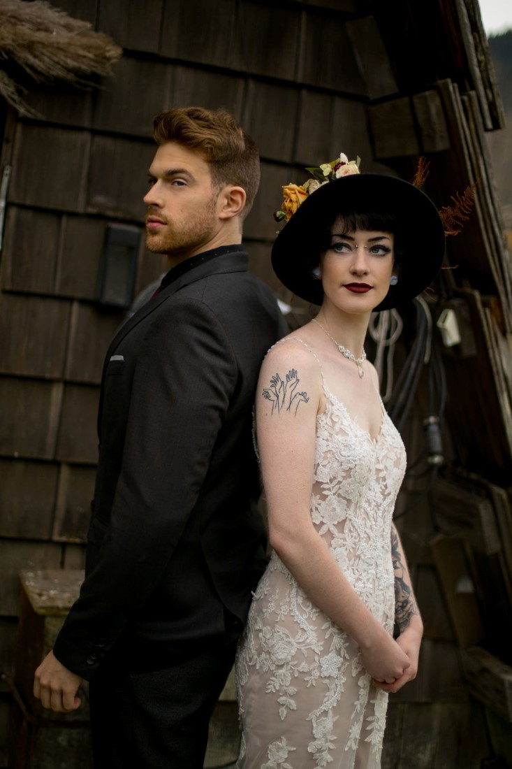 Tattooed Newlyweds stand back to back in front of cabin in Vancouver
