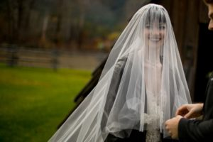 Bride smiles through cathedral veil wearing black leather jacket