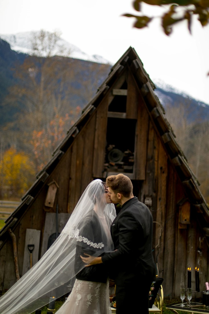 Bride and groom kiss in front of cabin and mountains wearing black leather jackets