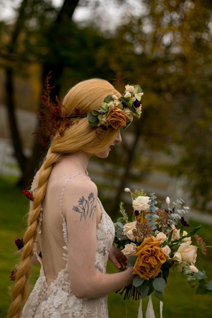 Bride wearing braid wig and floral crown by Meghan Andrews Photography