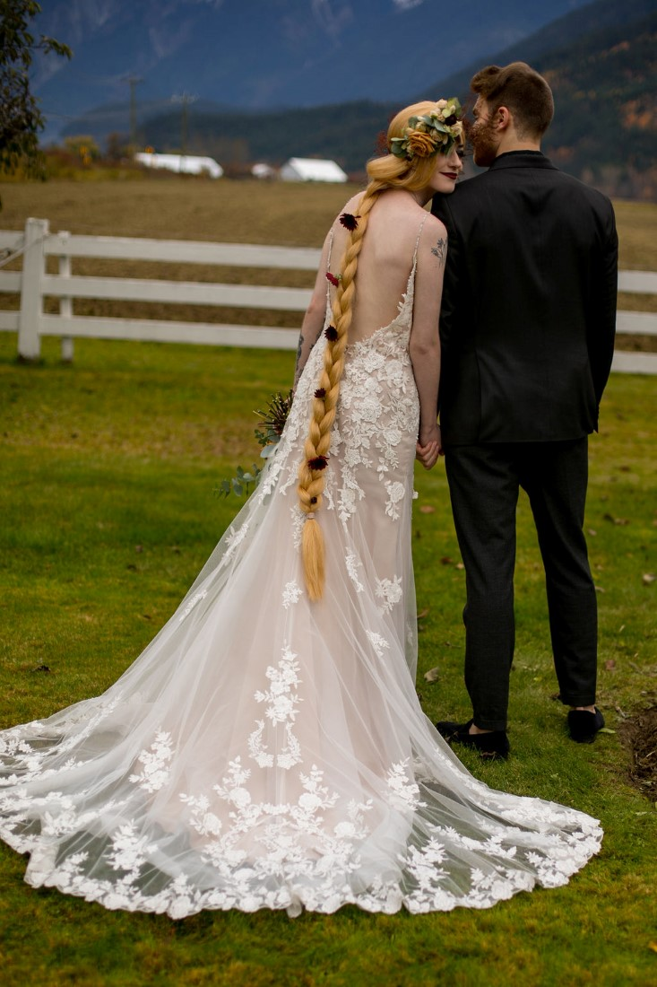 Breathtaking Wedding Beauty couple shows off blonde braid and wedding gown train of lace