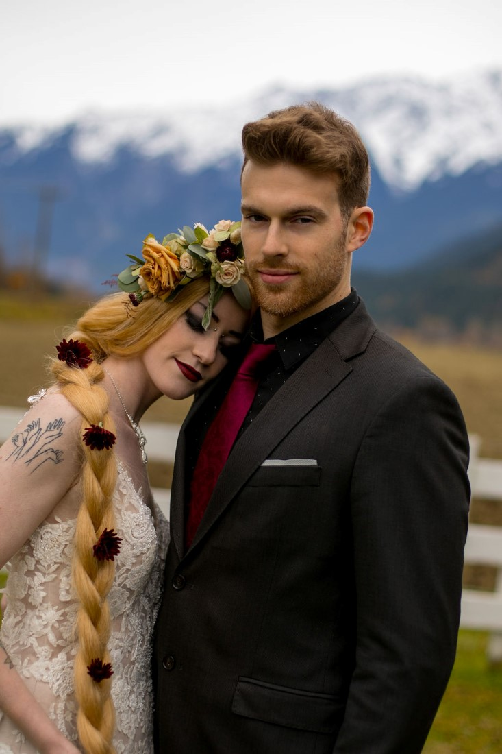 Bride leans on groom with BC mountains behind them