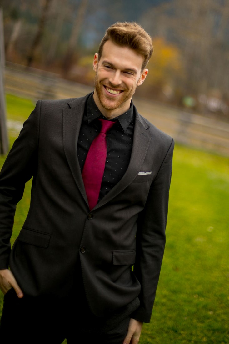 Groom in black suit and shirt with burgundy tie
