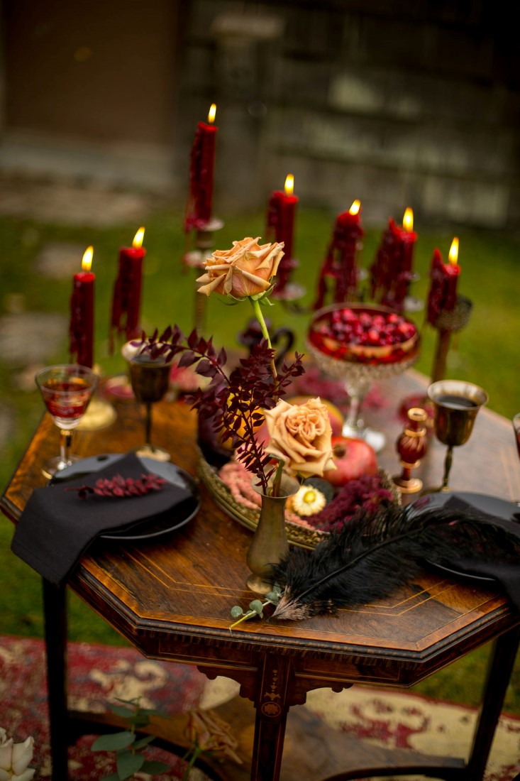 Tall candle sticks with burgundy candles and orange roses