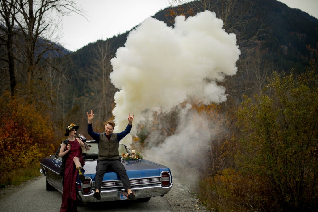 Smoke bomb behind blue classic car and newlyweds in BC mountains