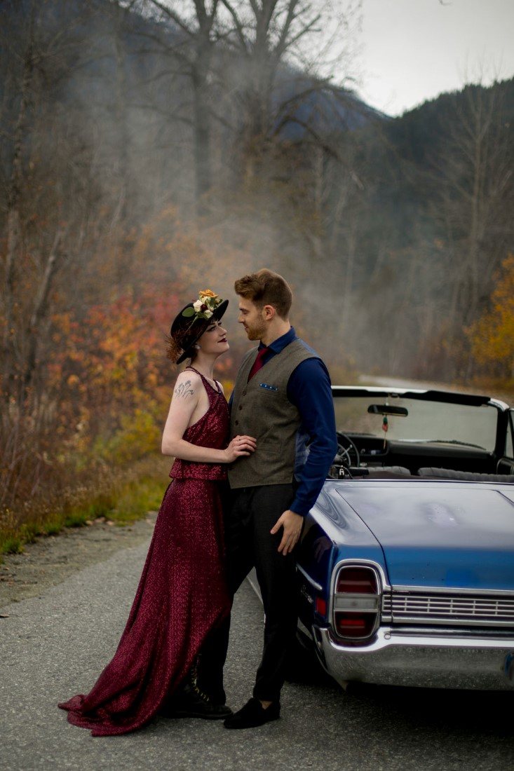 Newlyweds lean against blue classic car in Vancouver wedding