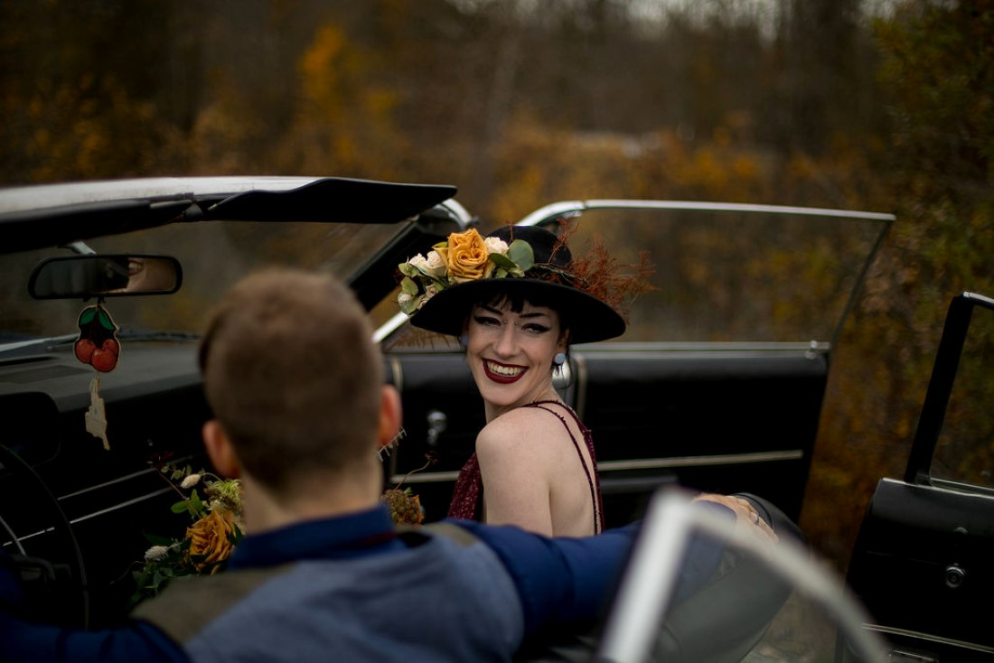 Bride smiles to camera wearing black hat with floral in classic car by Whisteria Events and Rentals