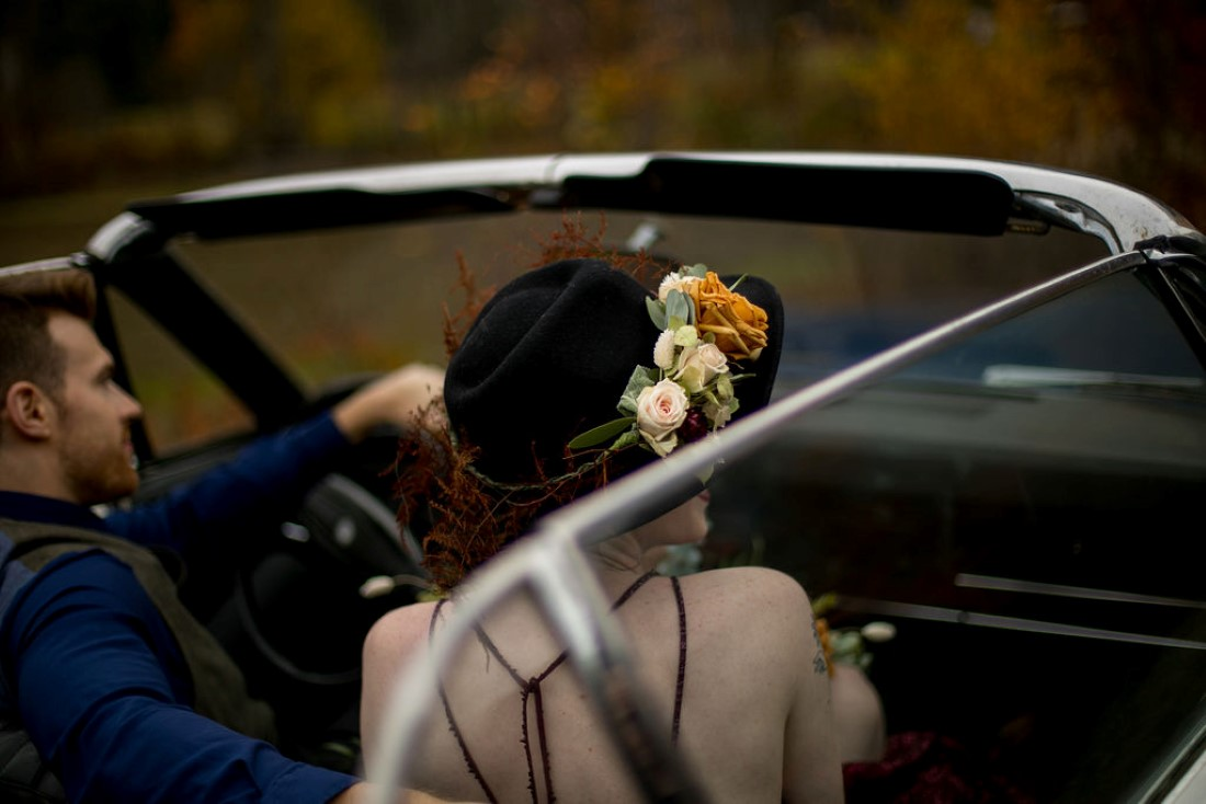 Bride wearing floral crown in classic car by Meghan Andrews Photography