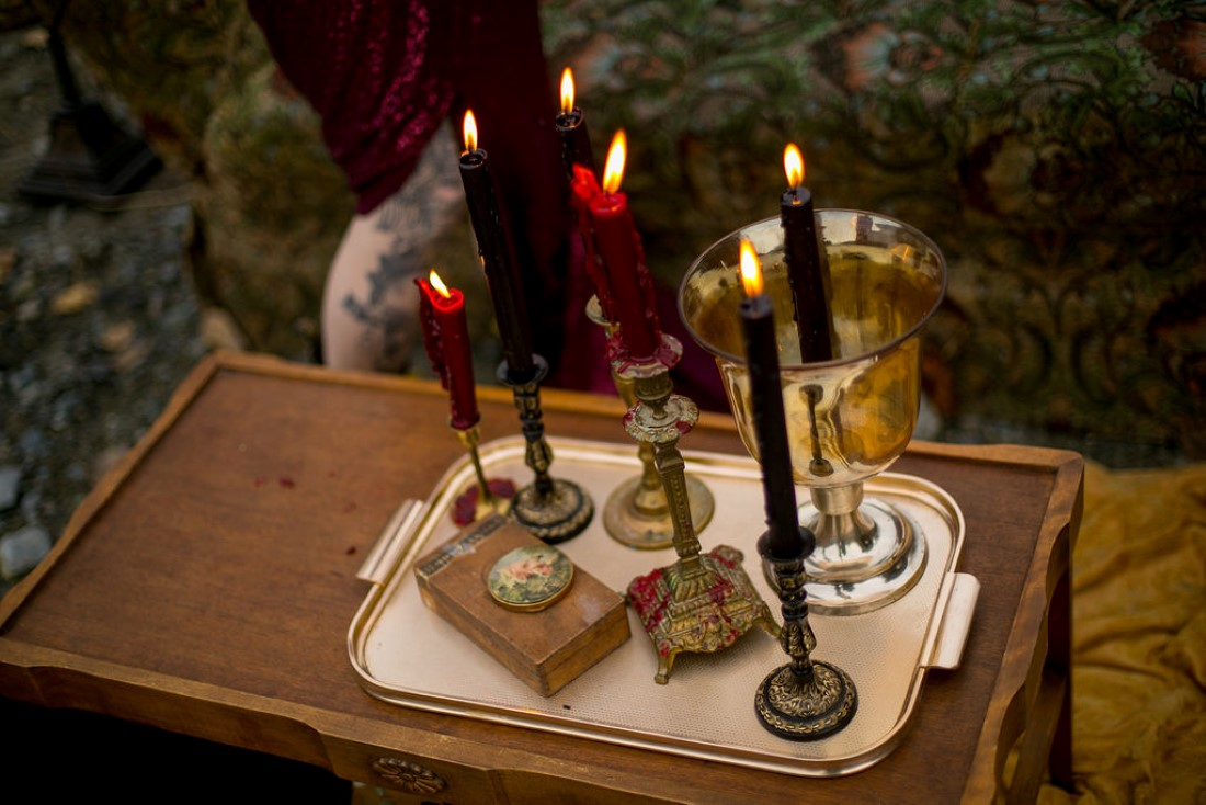 Burgundy candles in candelabras on wood table in British Columbia wedding