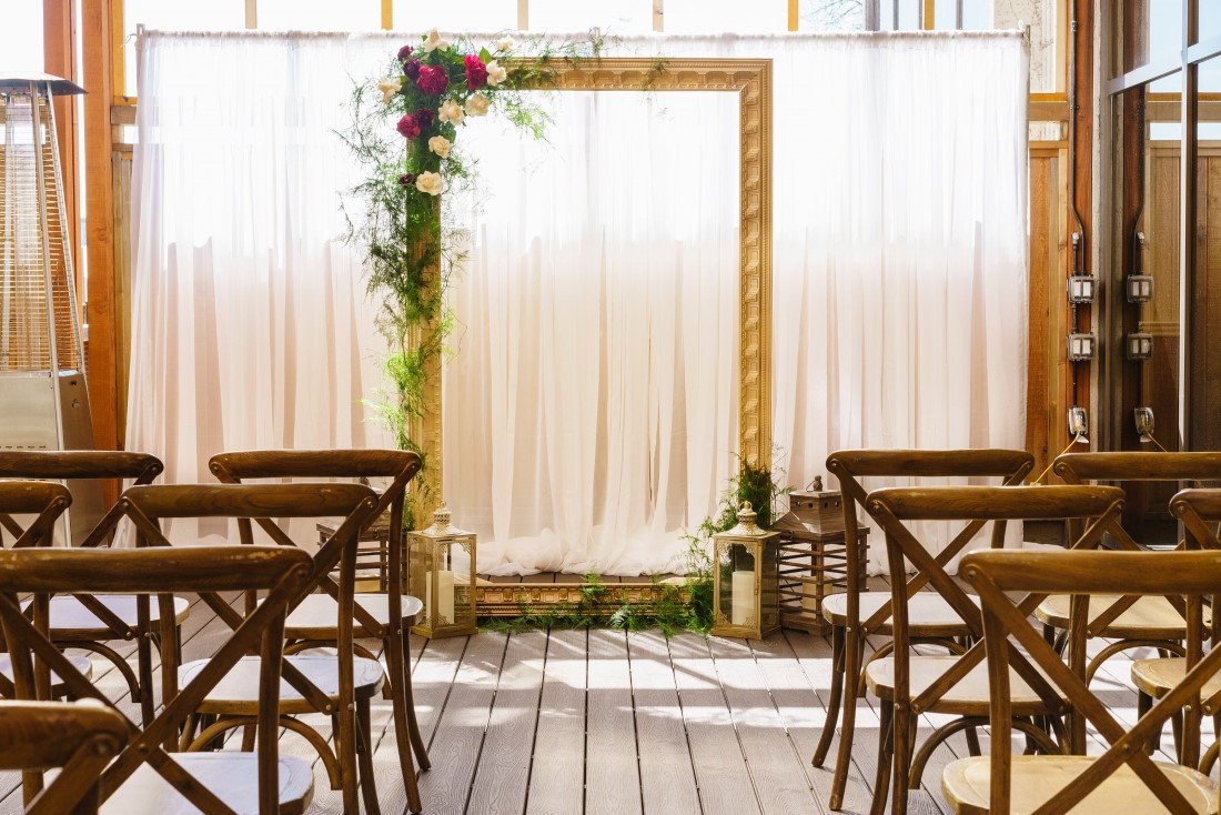 Frame with white fabric wedding ceremony backdrop
