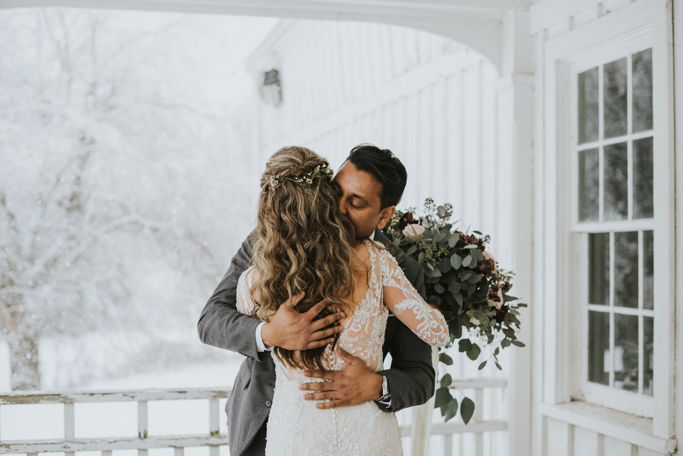 Groom kisses bride during first look on farmhouse porch with snow