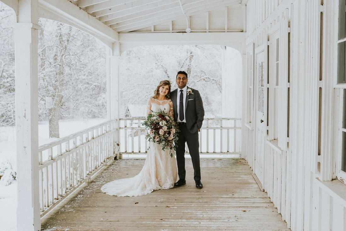 Bride and Groom on Farmhouse porch with snowstorm behind by White Canvas Photo