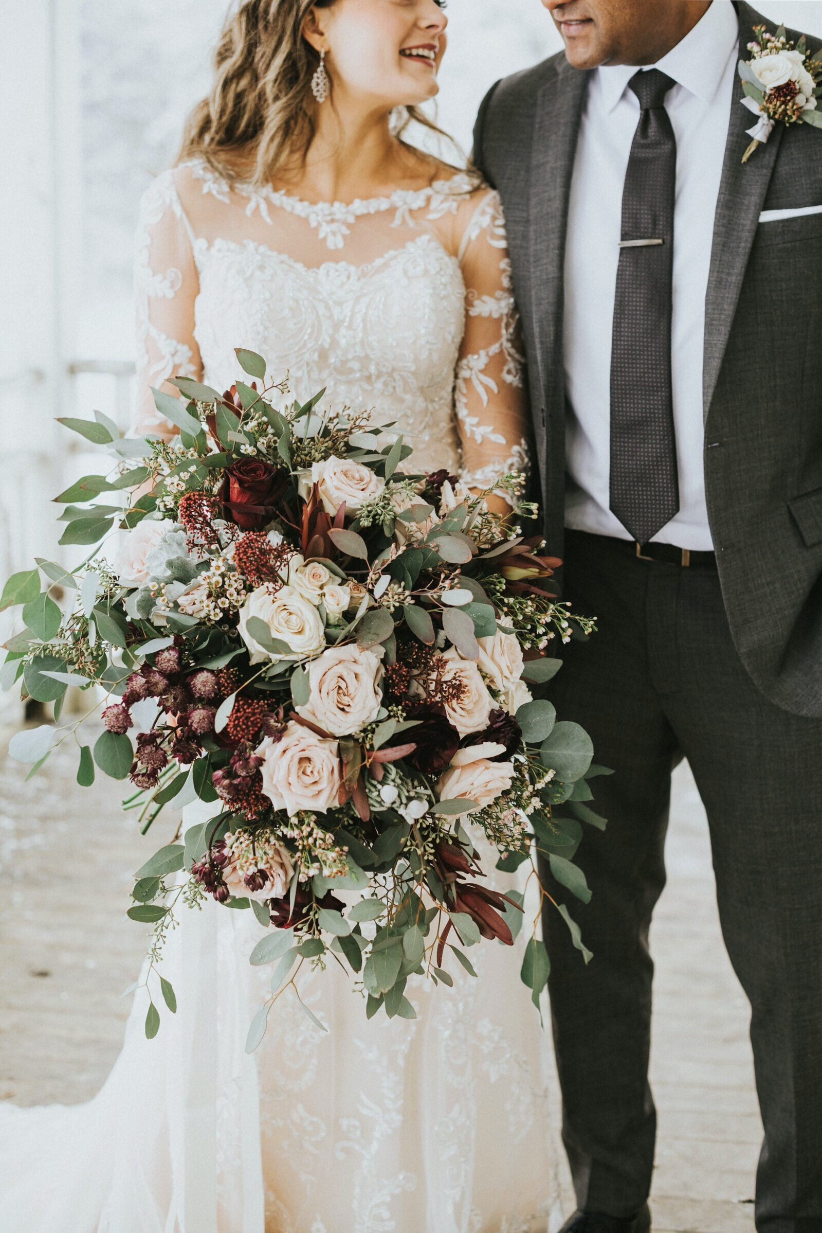 Bouquet of pink, white and burgundy roses, dusty miller, eucalyptus and wax flowers