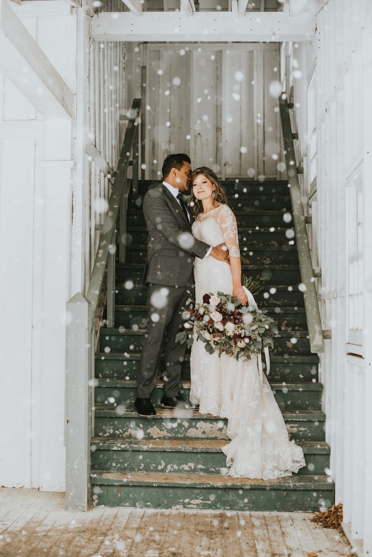 Snowy Urban Fairytale Wedding couple stand on stairs of barn with snowflakes all around