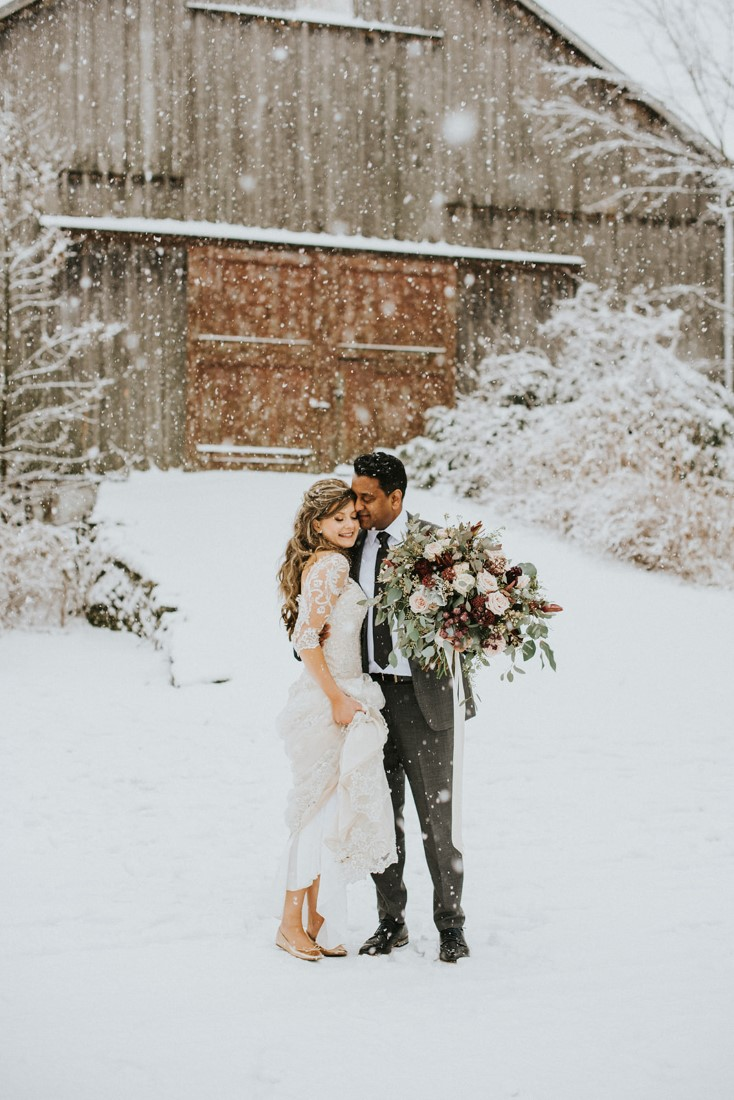 Bride and Groom stand in front of barn while large snowflakes fall on them