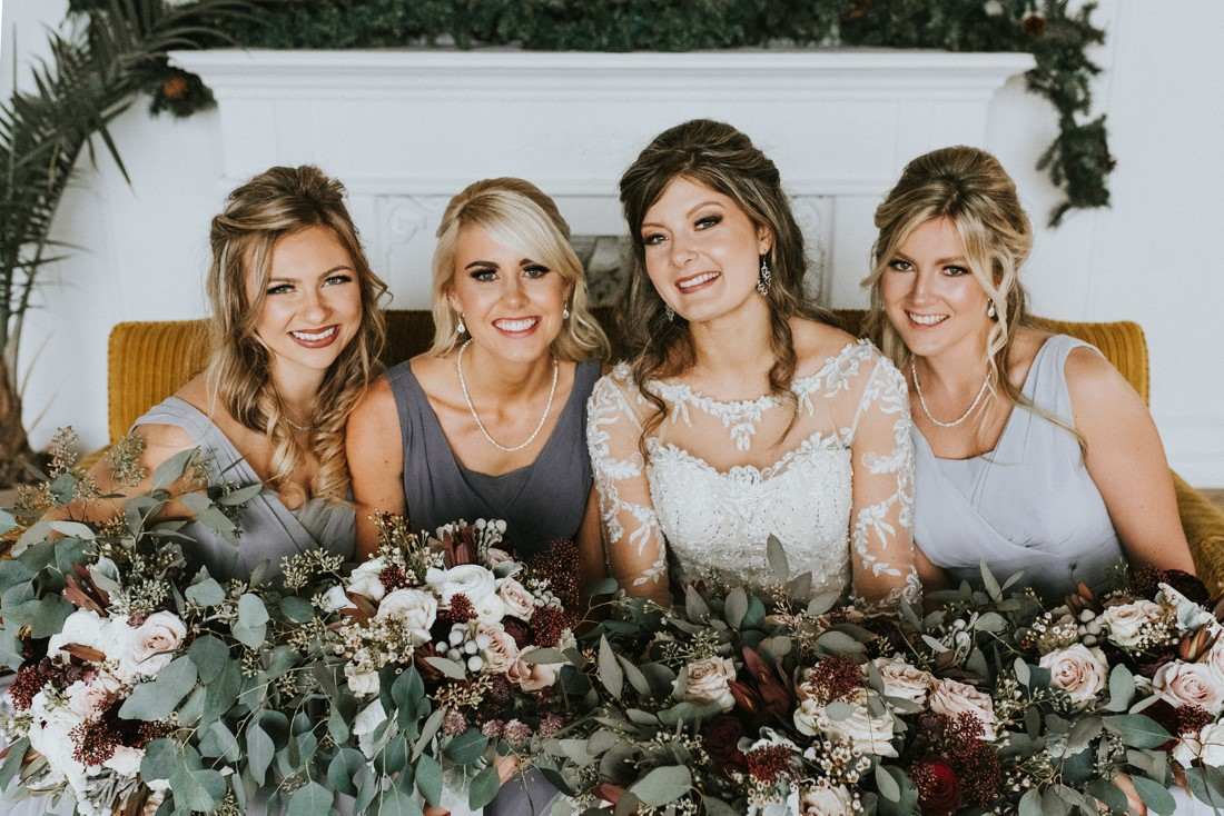 Bride and Bridesmaids hold bouquets of roses, eucalyptus and dusty miller