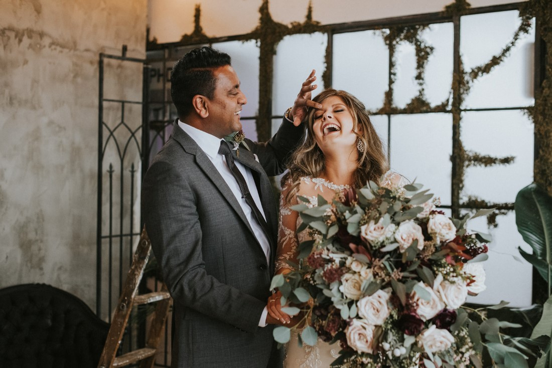 Newlyweds laughing as they take portraits